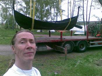 Who is the old man in front of the new boat?